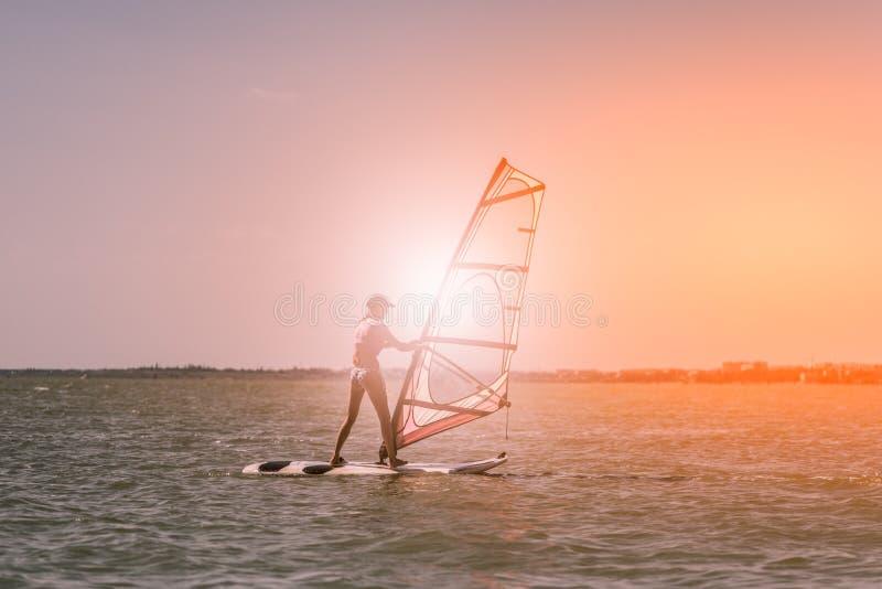 As velas magros atléticas novas da menina na windsurf placa no mar aberto em férias de verão no recurso windsurfing imagem de stock