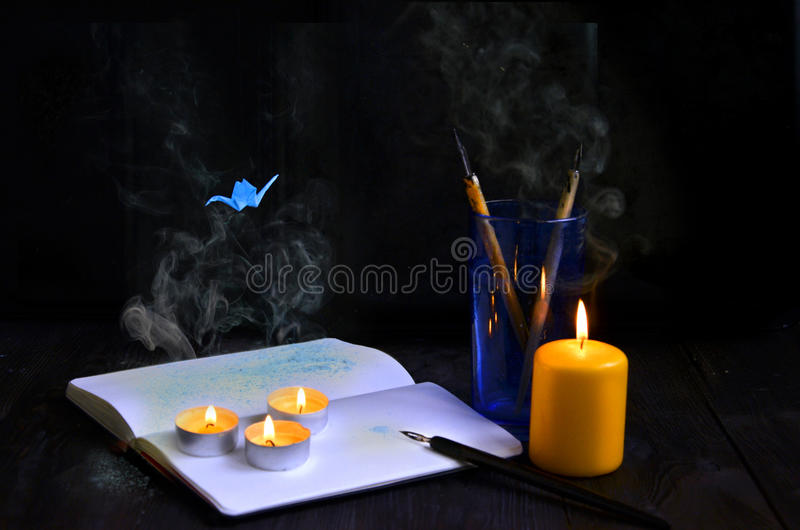 As velas no fundo de madeira velho com fumo e o origâmi crane foto de stock