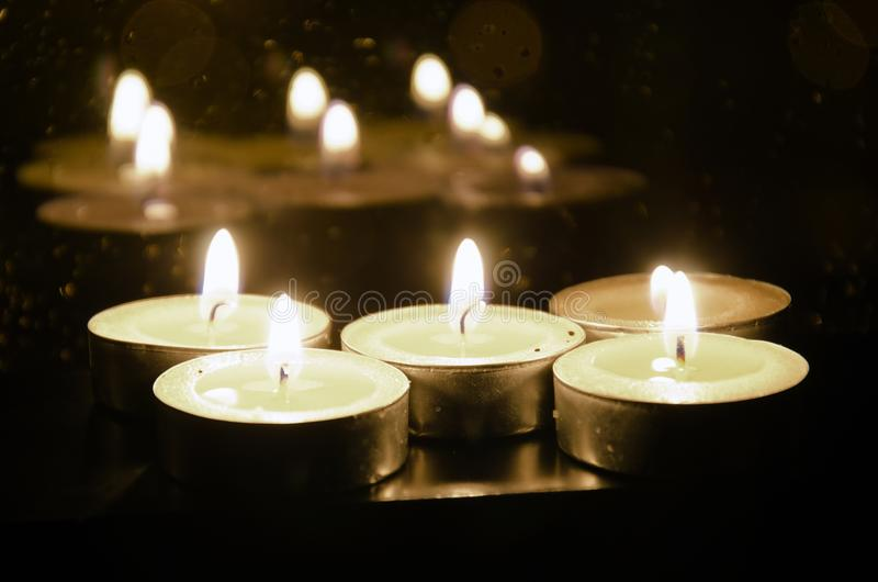 As velas pequenas ardentes são refletidas na janela atrás de que a escuridão do passo imagem de stock
