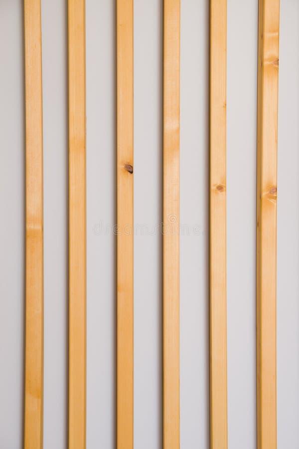 As venezianas verticais de madeira batten em uma luz - fundo cinzento da parede Detalhe interior, textura, fundo O conceito do mi fotografia de stock