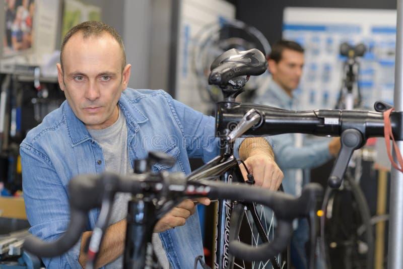As verificações do homem bike antes de comprar na loja dos esportes imagens de stock royalty free