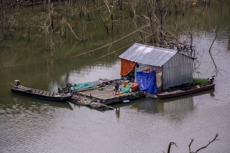 As vidas do pescador no meio do rio em uma casa da barraca feita de folhas da lata foto de stock royalty free
