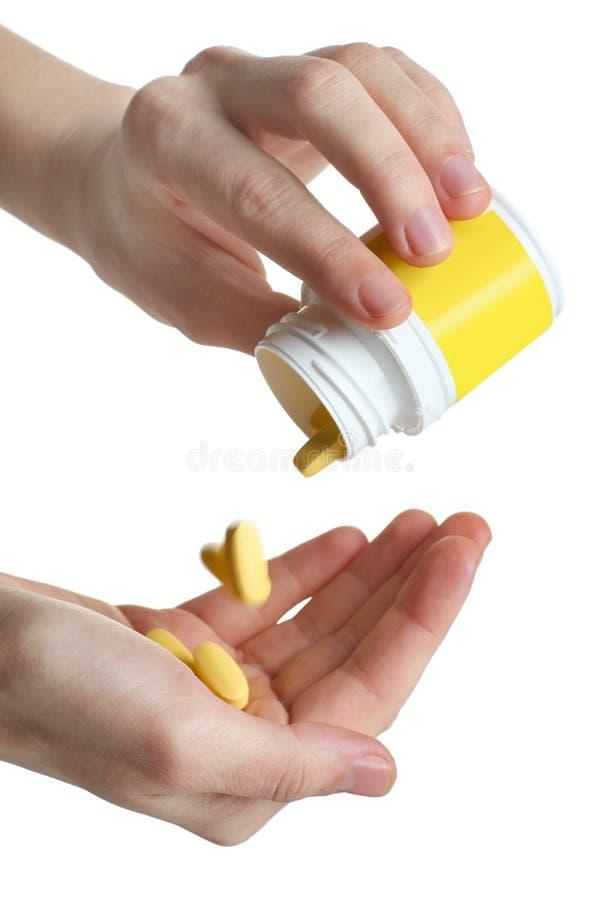 As vitaminas amarelas derramam na palma imagem de stock royalty free