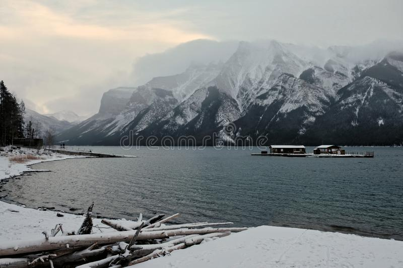 Beauty of Lake Minnewanka. As the wind blows more and more,the ground and mountain covered by snow. As it has not entered the deep winter, Lake Minnewanka royalty free stock photo