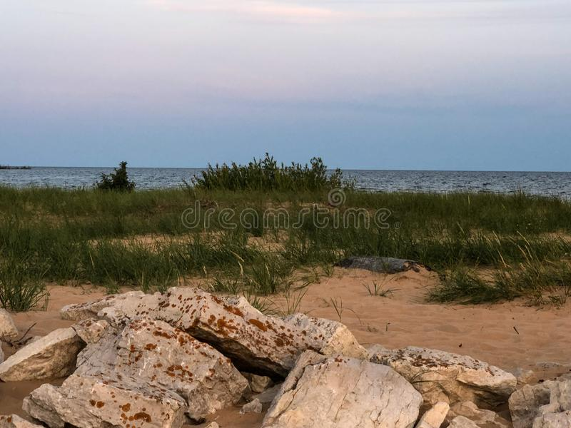 View of lake in Upper Michigan from shoreline with rocks. As you stand on the shoreline with the sand, green grasses, and rocks you have a great view of the stock photo