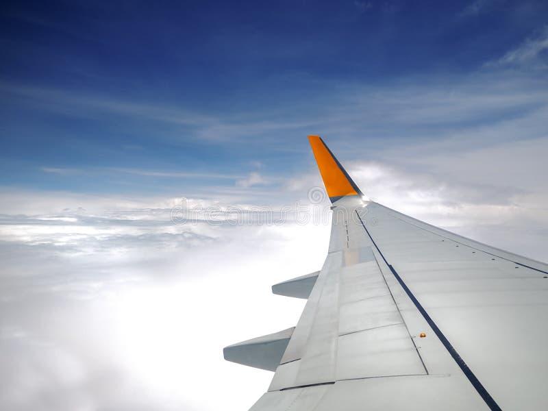 Asa de aviões sobre os céus azuis e as nuvens brancas, vista da janela durante o voo imagens de stock