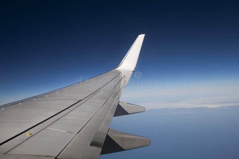 Asa de um plano do avião de passageiros em voo Céu azul fotografia de stock