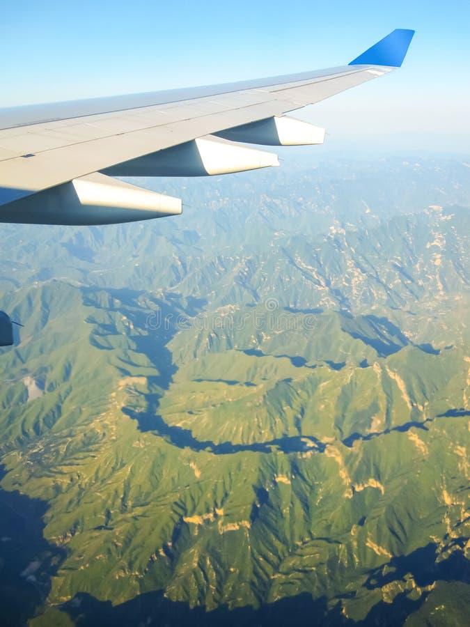 Asa de um voo do avião acima das montanhas Conceito de viagem Foto aplicada aos operadores do turismo imagens de stock royalty free
