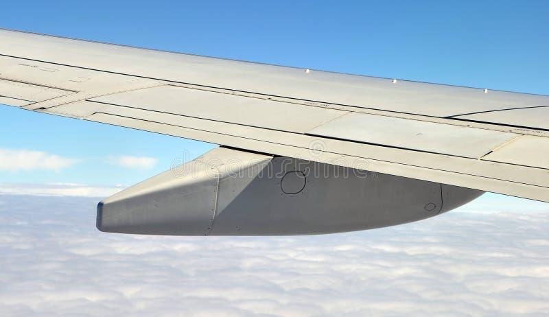 Asa do avião com os depósitos de gasolina sobre as nuvens fotos de stock