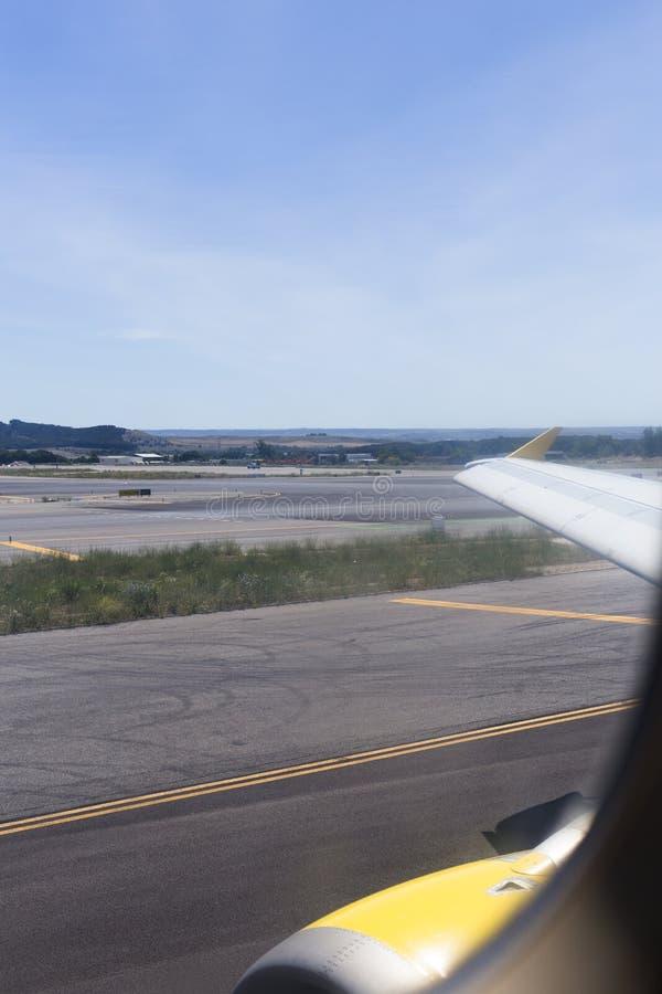 Asa do avião na pista de decolagem no aeroporto em um dia ensolarado Conceito do curso e dos feriados Vista do indicador foto de stock royalty free