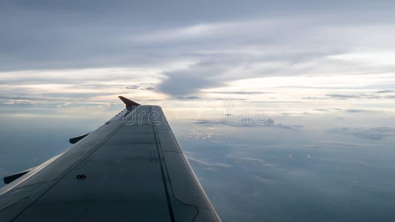 A asa do avião no nebuloso e no céu bonitos foto de stock royalty free