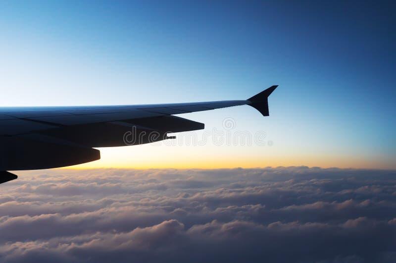 Asa do avi?o que voa acima das nuvens no c?u com por do sol fotos de stock royalty free