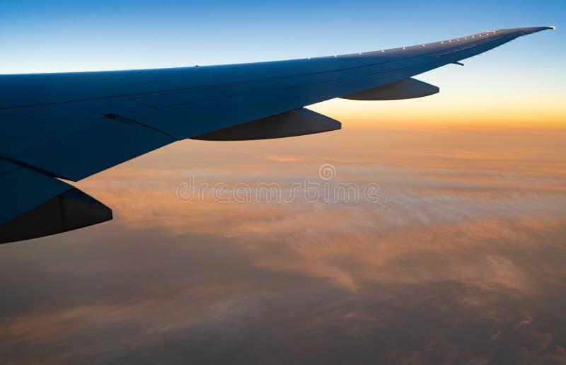 Asa do plano sobre as nuvens brancas Voo do avião no céu do nascer do sol Vista c?nico da janela do avi?o Voo da linha a?rea come fotos de stock royalty free
