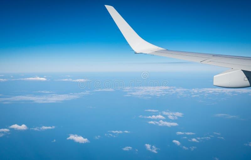 Asa do plano sobre as nuvens brancas Voo do avi?o no c?u azul Vista c?nico da janela do avi?o Voo da linha a?rea comercial plano imagens de stock