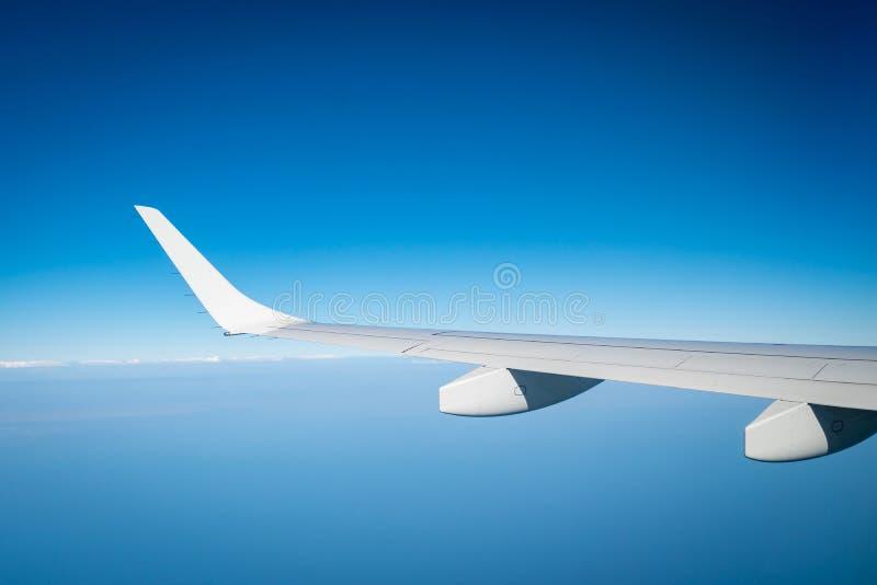 Asa do plano sobre as nuvens brancas Voo do avi?o no c?u azul Vista c?nico da janela do avi?o Voo da linha a?rea comercial plano foto de stock royalty free