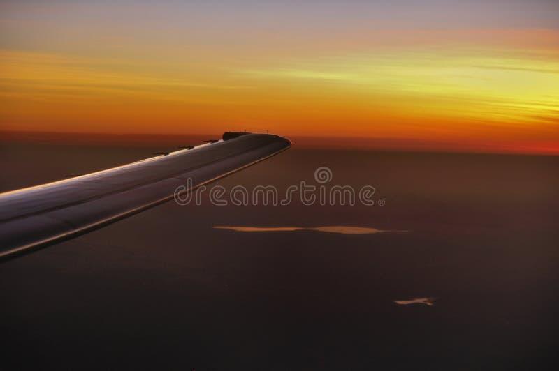 Asa dos aviões durante o por do sol fotografia de stock royalty free