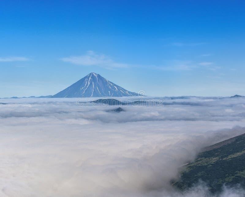 Asach vulkan i molnen i Kamchatka arkivfoto