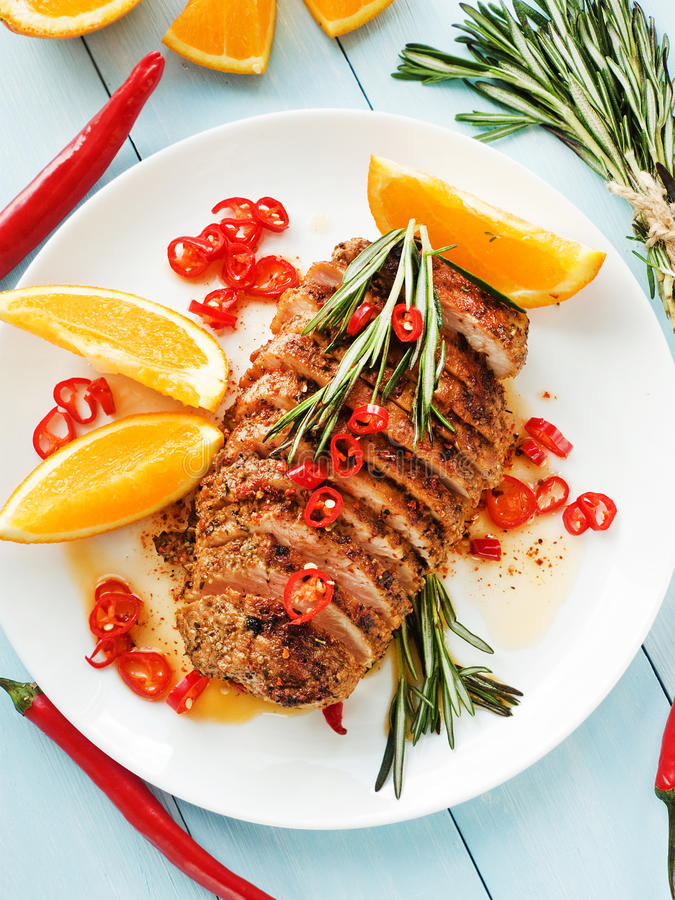 Asado. Argentinian Asado pork fillet with herbs, oranges and sauce. Shallow dof royalty free stock image