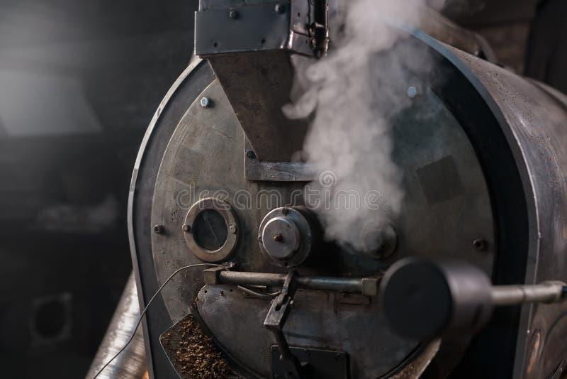 Asador del grano de café en el trabajo en un cuarto de la producción fotos de archivo
