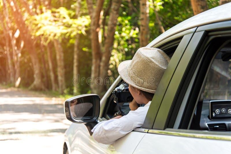 Asain妇女旅客拍与斜背式的汽车汽车的一张照片对在路森林的旅行 库存照片