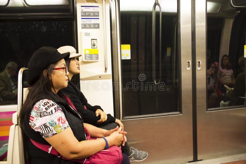 Asain妇女母亲和坐在旅途的地铁里面的女儿旅客在巴黎市附近 免版税库存照片