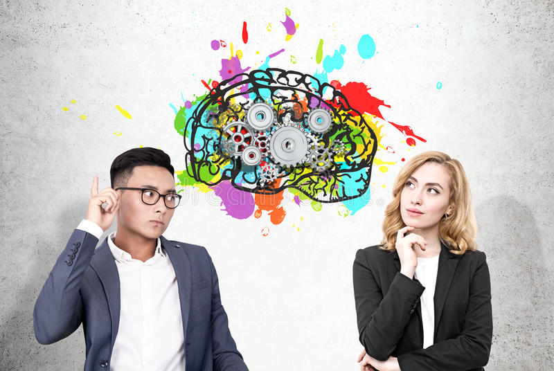 Asain man and woman and brain with cogs. Portrait of an Asain businessman and a blond women standing near a concrete wall with a colorful brain sketch and cogs royalty free stock image
