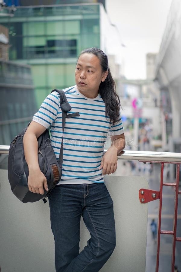 Asain / Thai-Chinese long black hair guy with blue line t-shirt is thinking and holding backpack on his sholder near the sky train stock images
