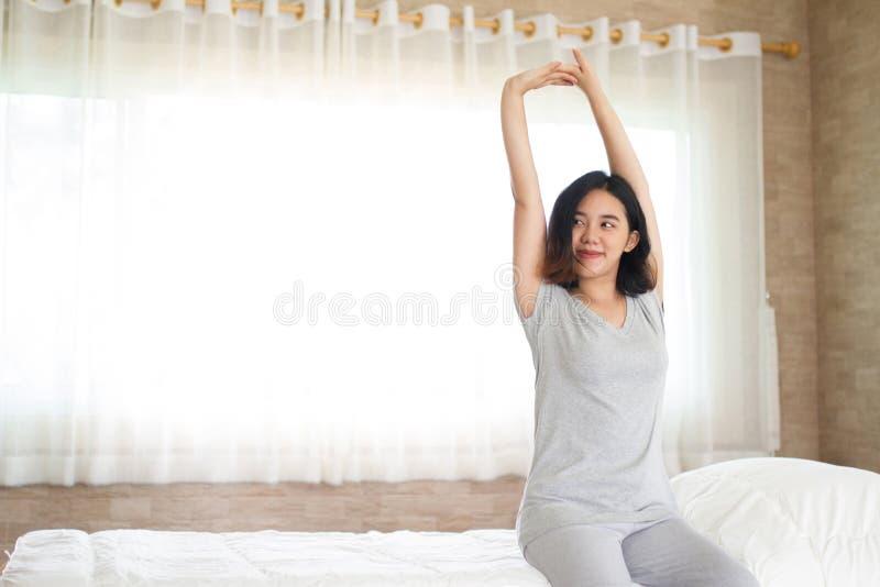 Asainmeisje het uitrekken zich in bed stock foto's