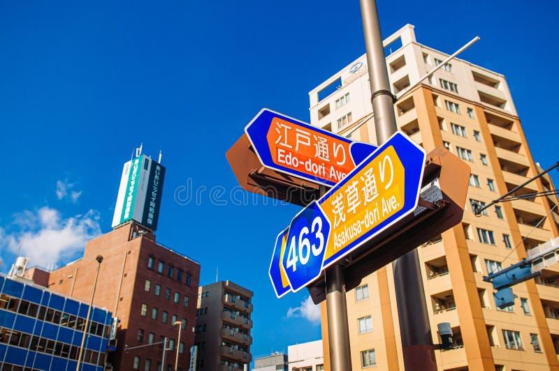 Asakusadori en Edo-dori de Wegstraat ondertekent met gebouwen tegen heldere blauwe hemeldag stock fotografie