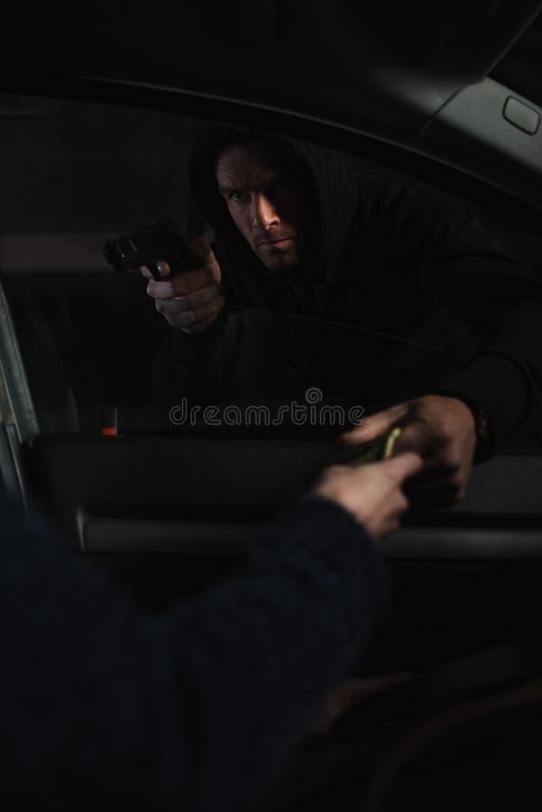 asaltante de sexo masculino que apunta por el arma en mujer foto de archivo