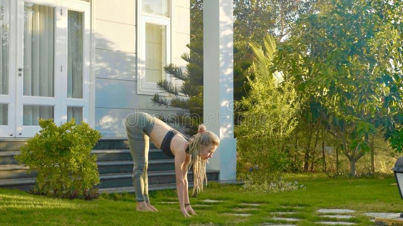 asana瑜伽专业表现由一个女孩的她的房子后院的  库存照片