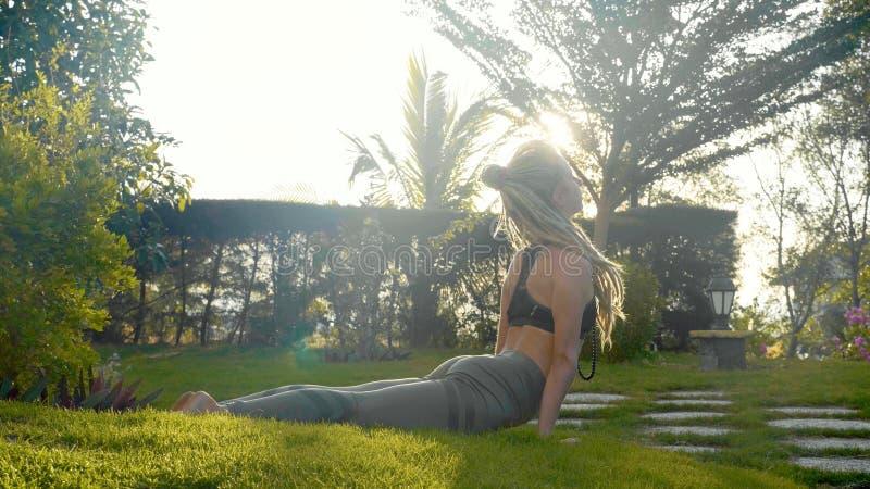 asana瑜伽专业表现由一个女孩的她的房子后院的  库存图片