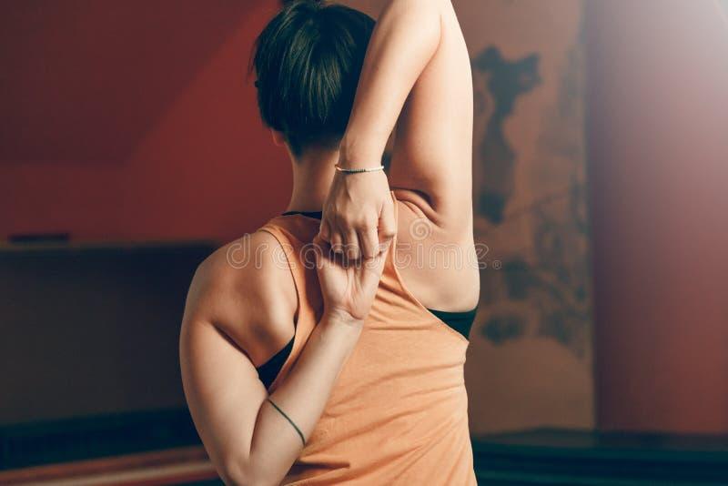 Asana bonito Gomukhasana da ioga das práticas da jovem mulher fotos de stock royalty free