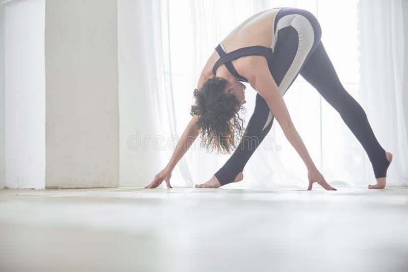 Asana bonito Parivrtta Trikonasana da ioga das práticas da jovem mulher - pose revolvida do triângulo no estúdio claro da ioga fotos de stock