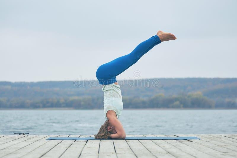 Asana hermoso Shirshasana - actitud de la yoga de las prácticas de la mujer joven del Headstand en la cubierta de madera cerca de imagenes de archivo