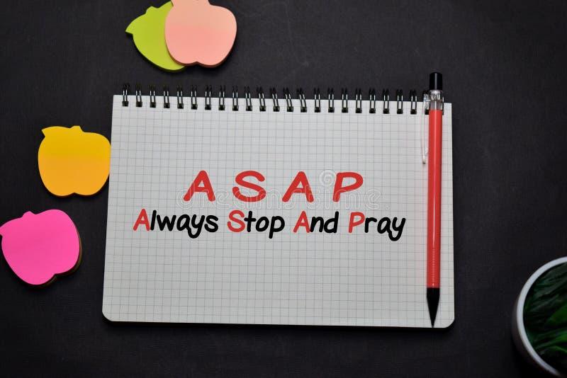 ASAP - Stoppa alltid skrivningen i en bok på skrivbordet Begreppet kristen tro royaltyfri bild