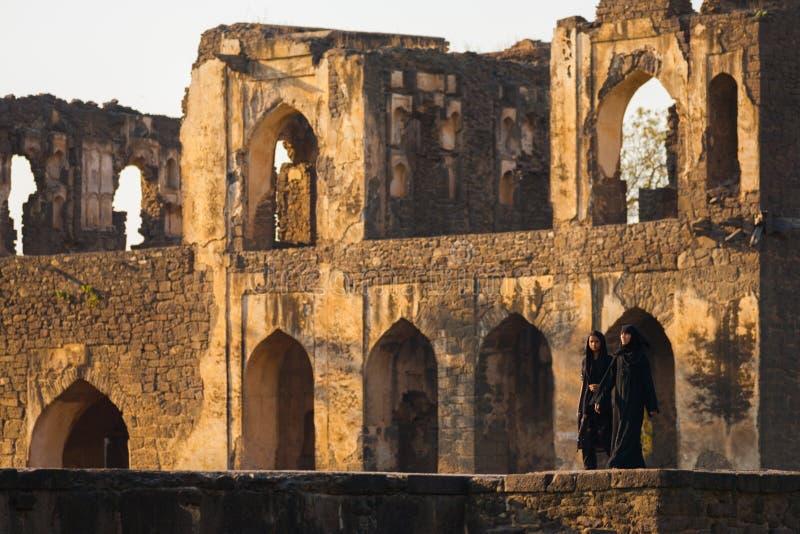 Asar Mahal Ruins Park Muslim Women Abaya Bijapur. BIJAPUR, INDIA - FEBRUARY 20, 2009: Unidentified Indian muslim women wearing abayas walk near the ruins of Asar stock images