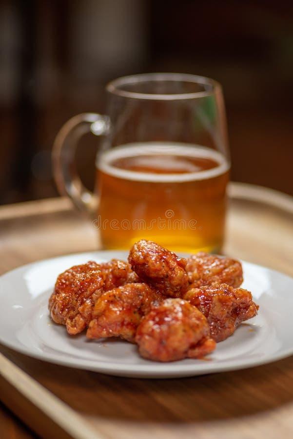 Asas de frango fritas quentes picantes sem ossos na placa com a caneca de vidro de cerveja foto de stock