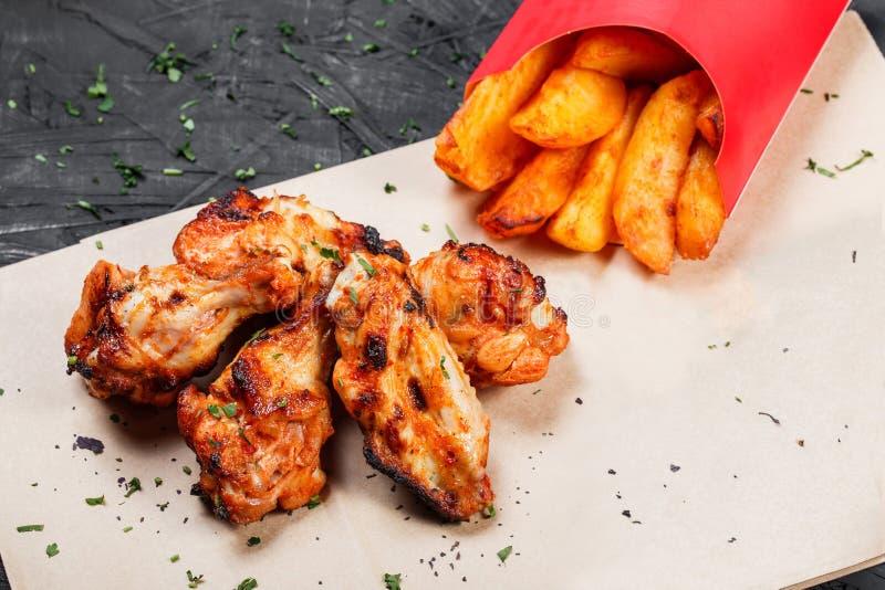 Asas de frango frito com as batatas cozidas no papel do ofício no fundo preto imagem de stock