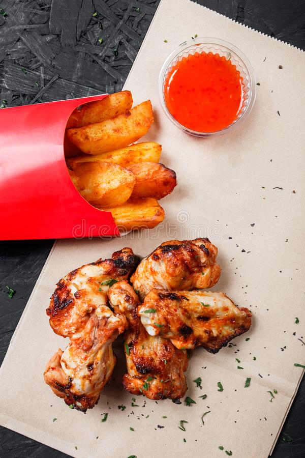 Asas de frango frito com batatas cozidas e molho do BBQ no papel do ofício no fundo preto fotos de stock royalty free