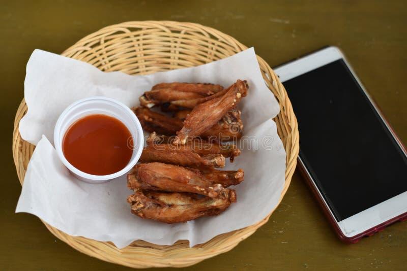 Asas de frango frito com mergulhos em uma cesta foto de stock