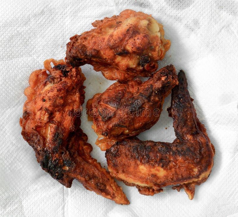 Asas de frango frito queimadas no fundo branco do tecido para reduzido o óleo imagem de stock