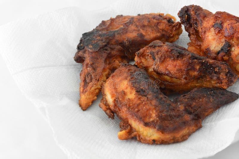 Asas de frango frito queimadas no fundo branco do tecido para reduzido o óleo imagens de stock royalty free