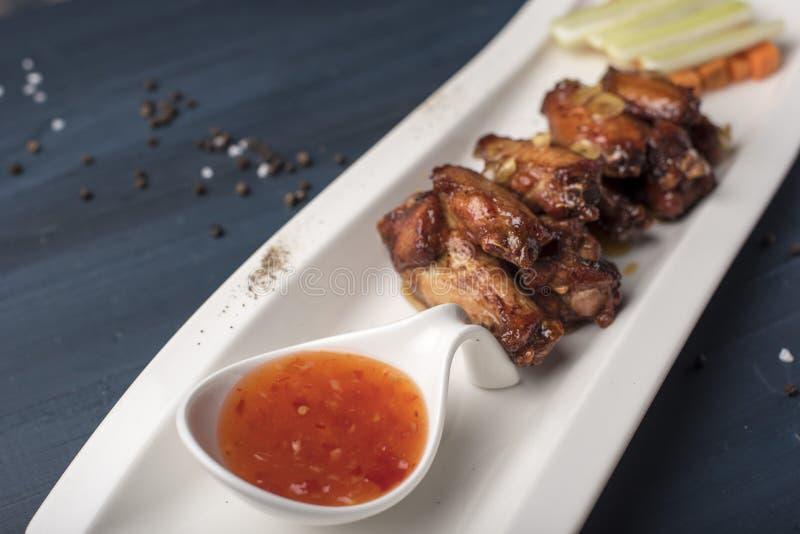 Asas de galinha cozidas com cenouras e aipo e molho de pimentão doce na placa branca imagens de stock royalty free