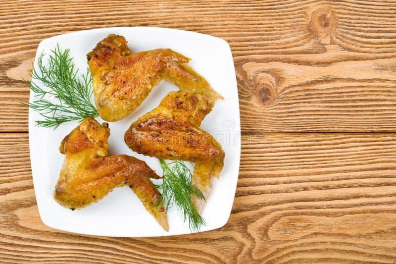 Asas de galinha cozidas em uma placa quadrada imagem de stock
