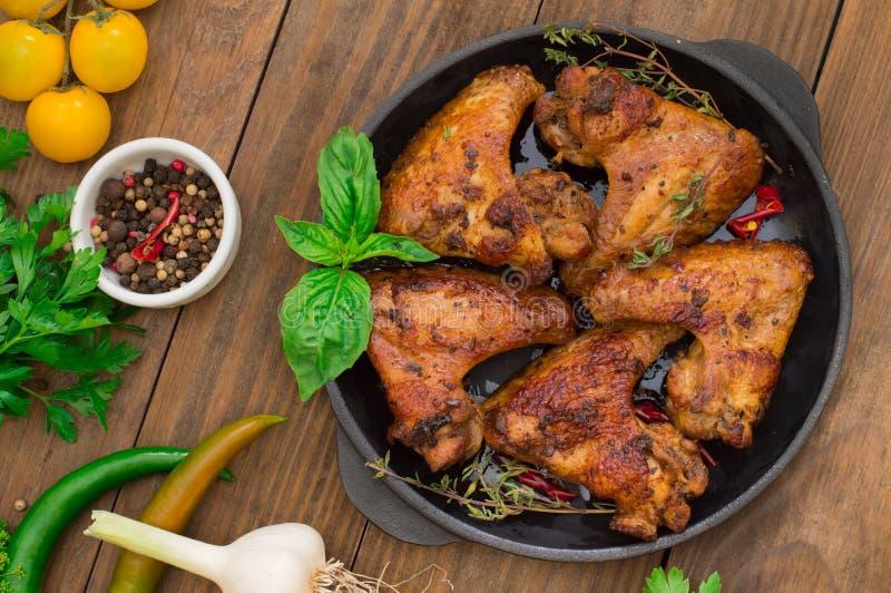 Asas de galinha cozidas na bandeja de cozimento Foco seletivo Fundo de madeira Close-up Vista superior fotografia de stock royalty free