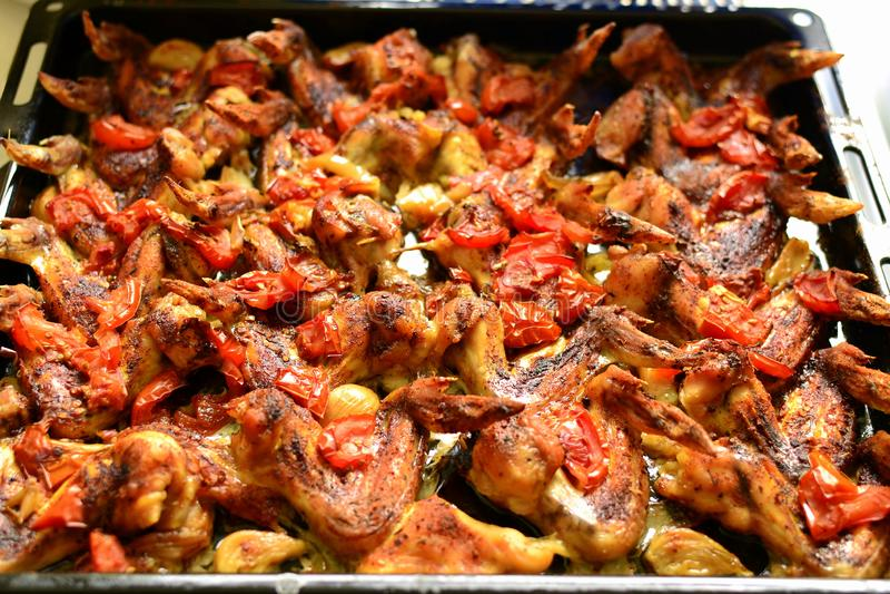 Asas de galinha cozidas na pimenta a com alho e tomate fotos de stock