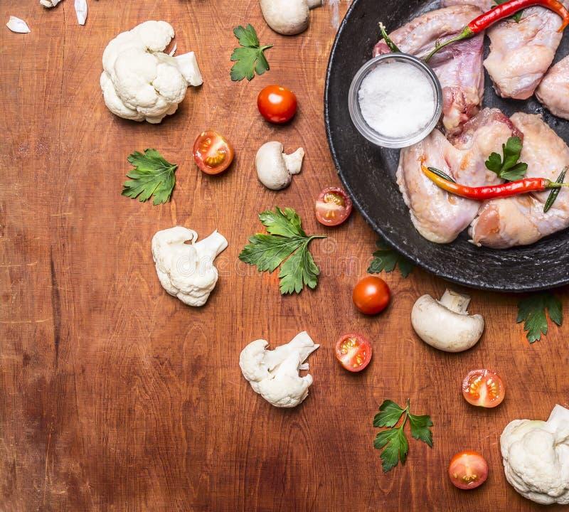 Asas de galinha cruas com as bandejas da pimenta vermelha e do sal, o ferro fundido com tomates e a couve-flor no rusti? clo de m fotografia de stock royalty free