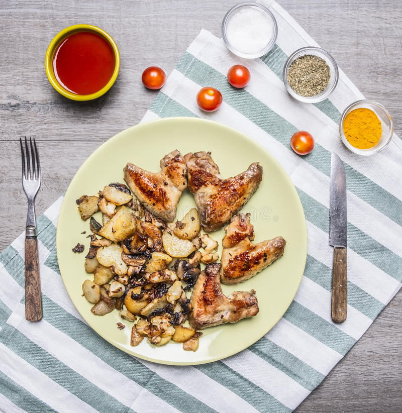 Asas de galinha deliciosas fritadas com molho de pimentão fritado das batatas e os tomates de cereja picantes temperados com uma  fotos de stock