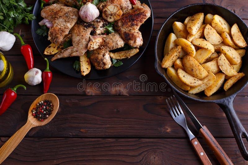 Asas de galinha grelhadas, batatas cozidas em uma bandeja, cutelaria, ervas a fotos de stock